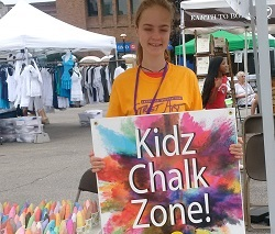 Smiling girl holding a sign Kidz Chalk Zone