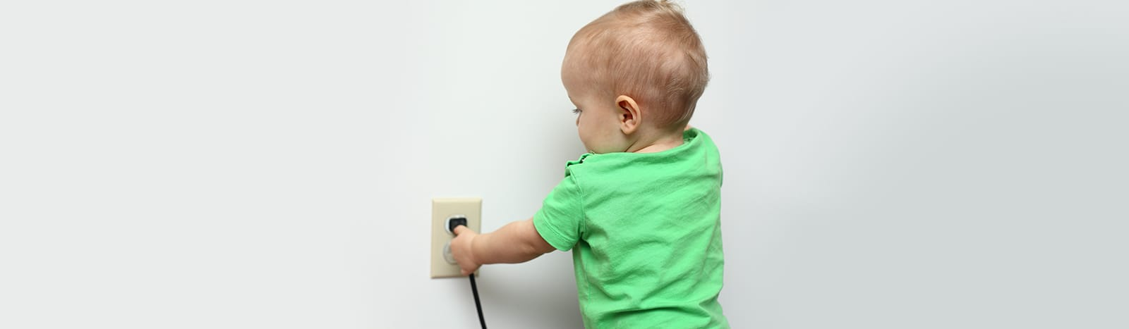 Young child playing with electrical plug outlet
