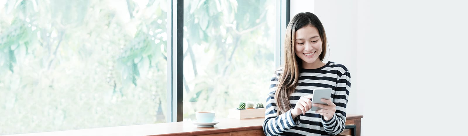 Asian woman sitting on window ledge looking at mobile device